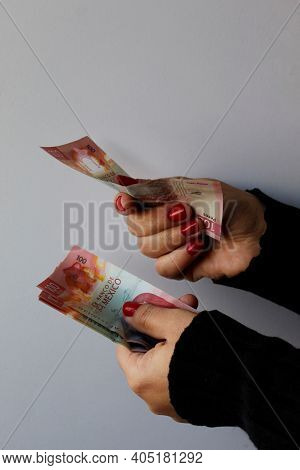 Hands Of A Woman Holding Mexican Banknotes Of 100 Pesos