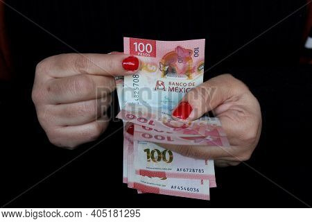 Hands Of A Woman Counting Mexican Banknotes Of 100 Pesos