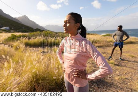 Fit african american couple in sportswear standing in tall grass. healthy lifestyle, exercising in nature.