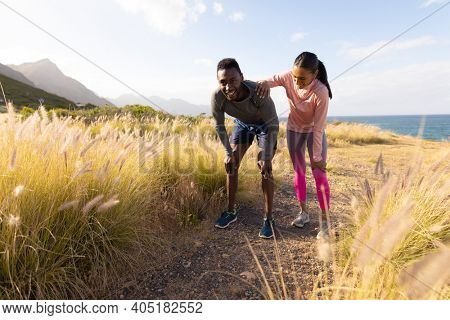 Fit african american couple in sportswear resting leaning on knees in tall grass. healthy lifestyle, exercising in nature.
