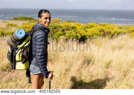 Portrait of fit african american woman wearing backpack nordic walking on coast. looking at the camera and smiling. healthy lifestyle, exercising in nature.