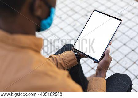 African american man wearing face mask using digital tablet. businessman in city health hygiene during coronavirus covid 19 pandemic.