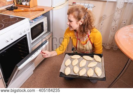 A Woman Puts Raw Russian Pies In The Oven For Baking. Homemade Baking.