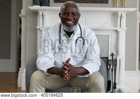 Portrait of senior african american male doctor giving patient consultation at home. healthcare at home in self isolation during quarantine lockdown.