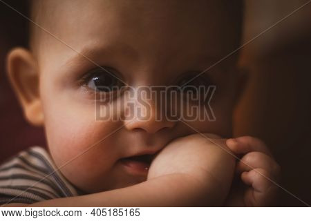 Teething In Babies. Small Caucasian Boy Is Holding His Fist In Mouth. Selective Focus. Close Up Phot
