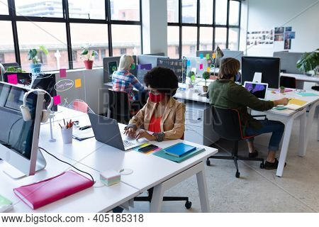 Diverse group of business people wearing face masks in creative office. group of people sitting at desks and using laptops. social distancing protection hygiene in workplace during covid 19 pandemic.