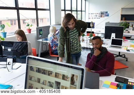 Two diverse businessmen working in creative office. men using computer and discussing work. business people and work colleagues at a busy creative office.