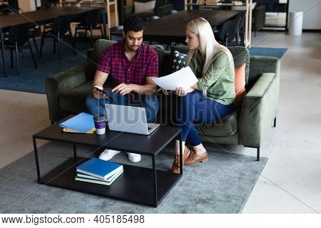 Two diverse business people working in creative office. two people sitting and discussing work. business people and work colleagues at a busy creative office.