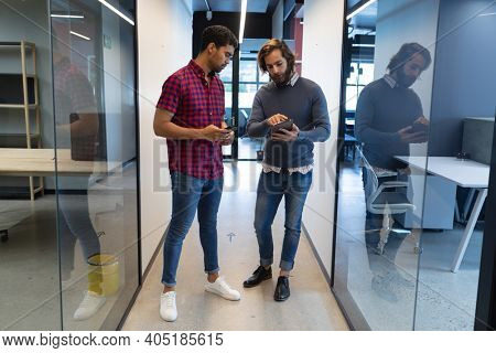 Two diverse businessmen working in creative office. two men standing and using tablet. business people and work colleagues at a busy creative office.