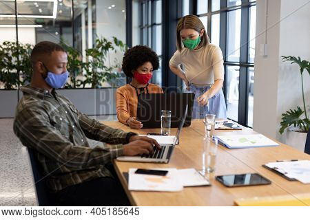 Diverse group of business people working in creative office. group of people wearing face masks and using laptops. social distancing protection hygiene in workplace during covid 19 pandemic.