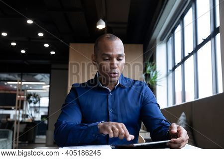 Mixed race businessman sitting having video chat using digital tablet in modern office. business modern office workplace technology.