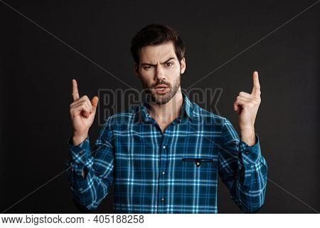 Perplexed handsome guy looking at camera and pointing finger upward isolated over grey background