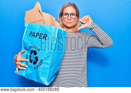 Middle age caucasian blonde woman holding recycling wastebasket with paper and cardboard with angry face, negative sign showing dislike with thumbs down, rejection concept