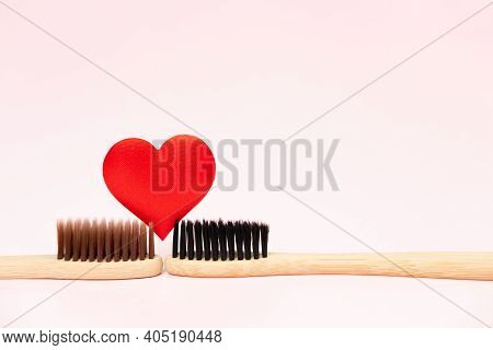Two Bamboo Toothbrushes With Red Heart On Pink Background With Copy-space. Biodegradable Bamboo Toot