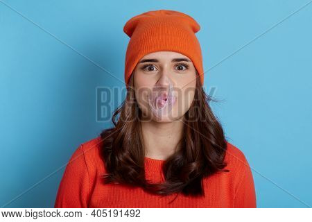 Young Lady Blowing Bubble Gum Isolated Over Blue Background, Happy Girl With Dark Hair With Burst Bu