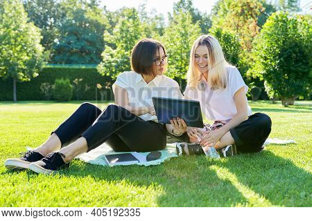 Woman Teacher, Psychologist, Social Worker Talking To Teenage Student Girl Sitting On Grass In Colle