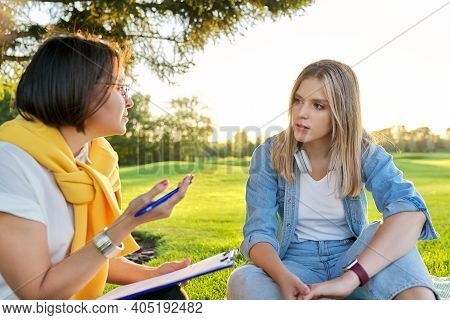 Conversation Of Young Woman With Psychologist, Social Worker, Outdoor At Meeting In Park On Lawn. Pr