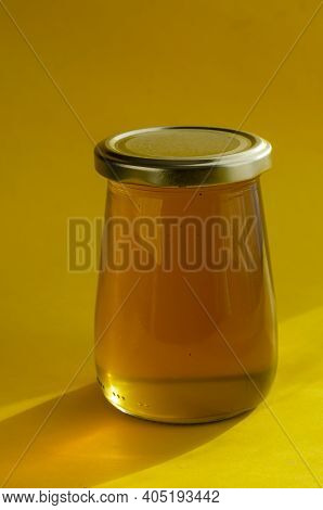 Natural Sugar Substitute, Healthy Food Concept. Raw Bee Honey In Glass Jar On Yellow Background.  Cl