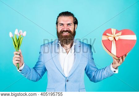 Bearded Hipster Hold Tulip Flower Bouquet. Holiday Present Concept. Brutal Handsome Man With Love Gi