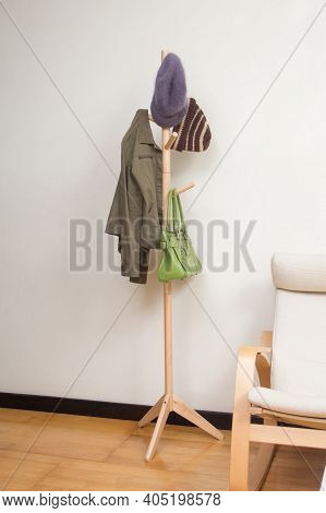 Wooden Coat Rack With Jacket, Hats And Handbag In The Room Background