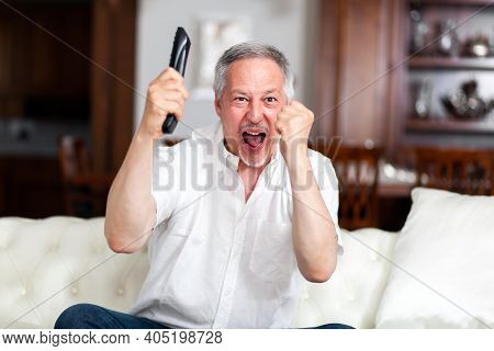 Ecstatic man exultating while watching a match at the tv