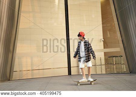 Fifteen-year-old Teenage Asian Boy Skateboarding In Front Of Modern Building