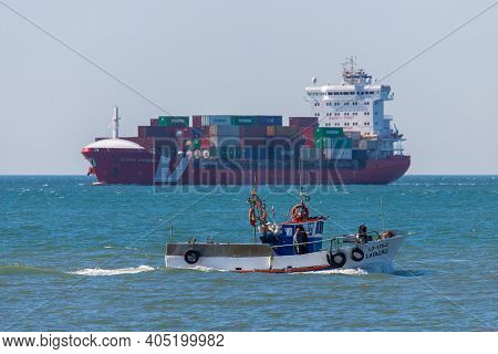 Portugal, Lisbon, October 08, 2018: Small Motor Boat In Sea On Background Container Ocean Ship.