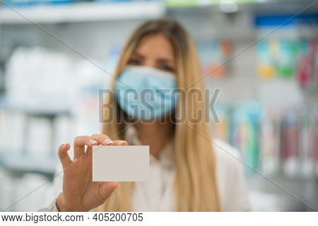 Female young pharmacist masked for covid or coronavirus pharmacist showing a blank business card