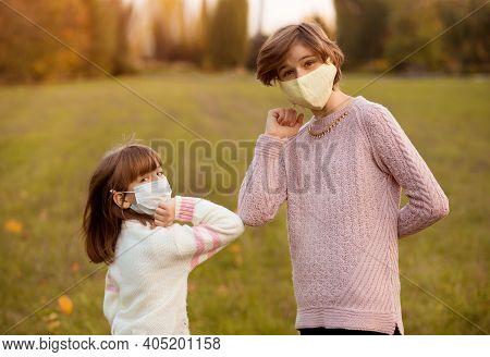 Two Girls Bump Elbows To Avoid Coronavirus Outdoors. Greeting During Coronavirus Epidemic. Health Ca