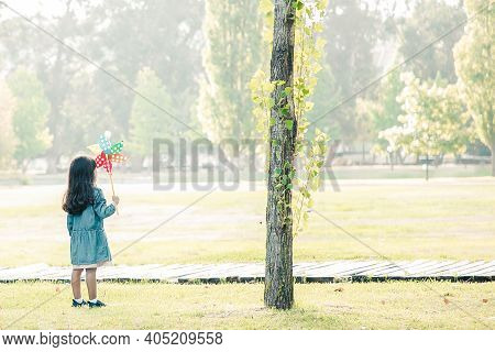 Black Haired Little Girl With Pinwheel Standing On Grass In Park. Green Trees And Sunshine In Backgr