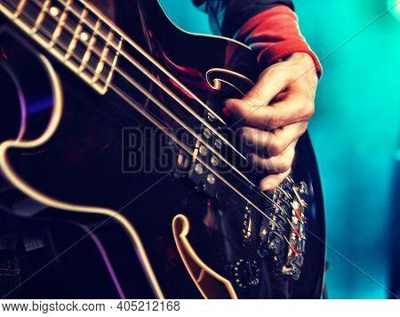 Closeup of a hand playing the bass guitar