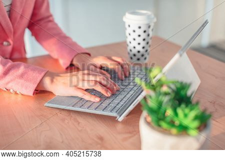 Working woman typing on laptop keyboard at home or office work desk. Closeup of hands with computer, coffee cup, tabletop succulent plant. Businesswoman in pink suit.