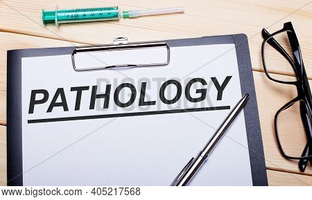 The Words Pathology Is Written On A White Piece Of Paper Next To Black-rimmed Glasses, A Pen And A S