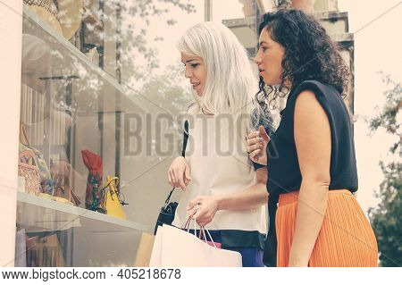 Excited Female Friends Staring At Accessories In Shop Window, Holding Shopping Bags, Standing At Sto