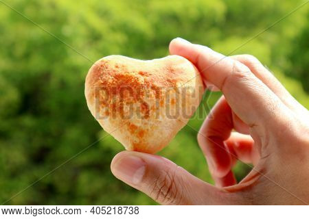 Man's Hand Holding A Heart Shaped Homemade Pao De Queijo Or Brazilian Cheese Bread With Blurry Green