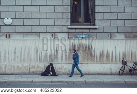 Germany, Munich,maximilianstr - July 25, 2013: Successful Man With Classic Suit Walking Past Homeles