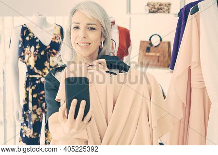 Woman Shopping In Fashion Store And Consulting Friend On Cellphone, Showing Chosen Dress At Frontal