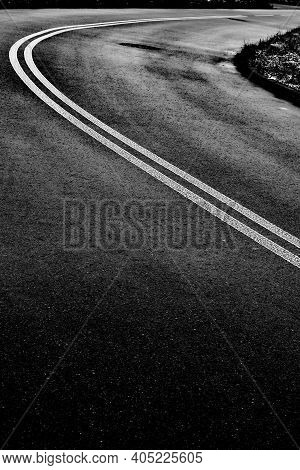 Black Tarmac Street Curve With White Double Solid Line