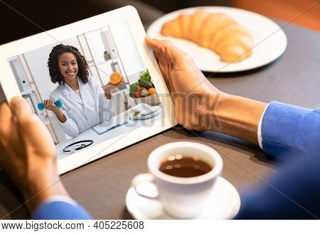 Black Dietologist Doctor Lady Consulting Patient Online Via Video Call On Digital Tablet. Unrecogniz