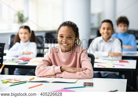 Elementary Education. Portrait Of Happy Small African American Girl Sitting At Table In Classroom At
