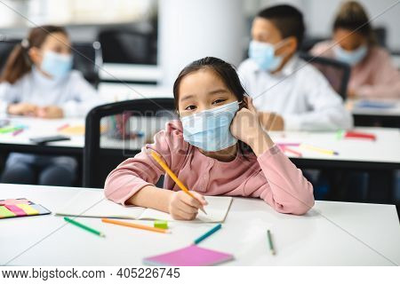 Education And Studying Concept. Portrait Of Small Asian Pupil Sitting At Desk In Classroom At School