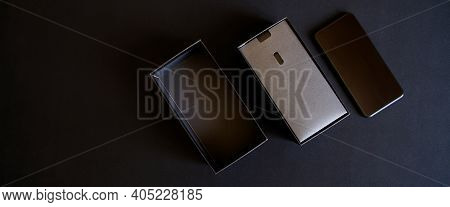 Unboxing A Black Smartphone Out Of The Box On A Dark Background. Modern Technologies. View From Abov