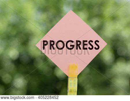 Progress - Text On Pink Note Paper On Green Background.