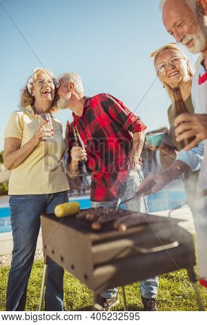 Group Of Happy Elderly People Having A Poolside Backyard Barbecue Party, Gathered Around The Grill,