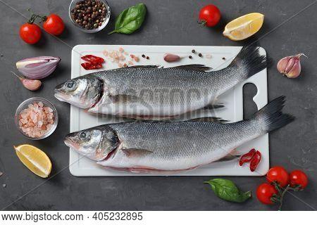 Raw Seabass With Ingredients And Seasonings Like Basil, Lemon, Salt, Pepper, Cherry Tomatoes And Gar
