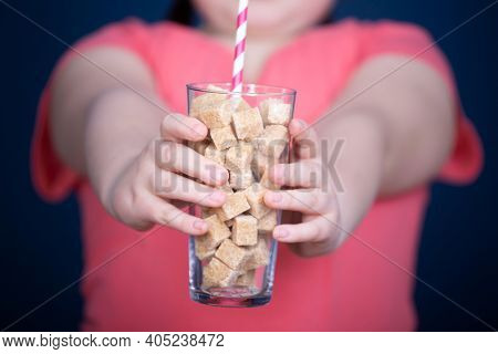 Child holding a glass full of sugar cubes. Everyday sugar usage among children concept