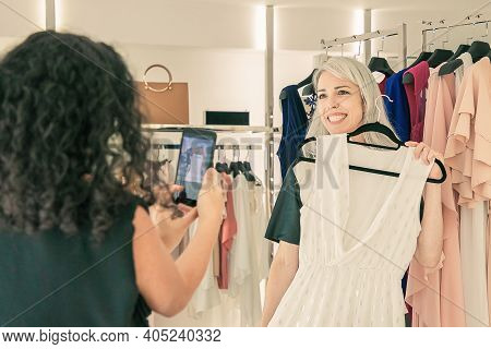 Cheerful Female Shoppers Enjoying Shopping In Clothes Store Together, Holding Dress, Posing And Taki