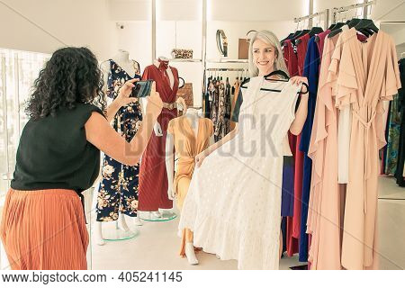 Excited Female Friends Enjoying Shopping In Fashion Store Together, Holding Dress And Taking Picture