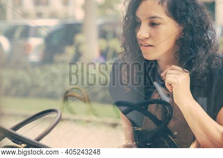 Focused Female Shopper Staring At Accessories In Shop Window, Holding Shopping Bags, Standing At Sto