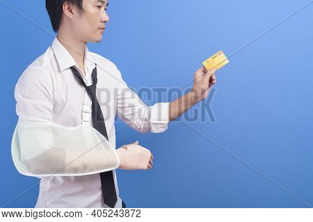 Young Businessman With An Injured Arm In A Sling Holding A Credit Card Or Medical Insurance Card Ove